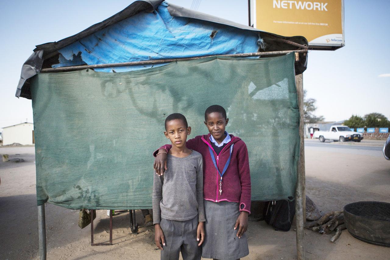 Vianda Tjipura, 11, and her brother Boy Tjipura, 10, outside their mother's roadside restaurant in Okakarara. Both are descendants of Herero survivors of the German genocide.