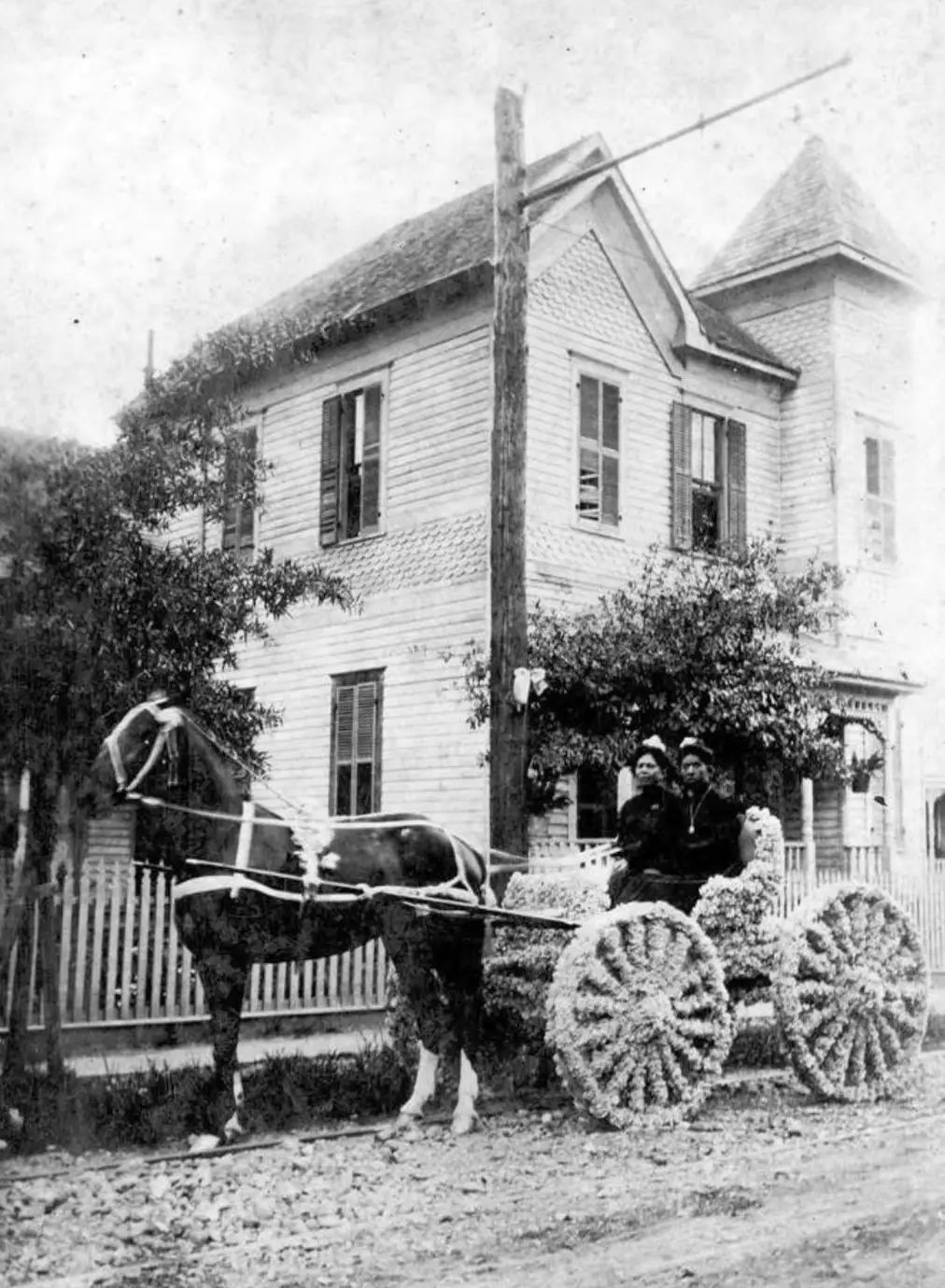 Two women in a decorated carriage, on Robin Street, Houston. ca. 1900